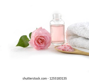 pile of pink rose blossoms with towel, salt in spoon, bottle oil on white background