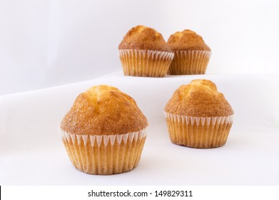 pile of plain muffins on a white background