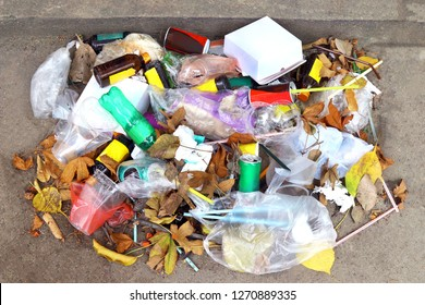 pile of plastic garbage waste on the floor, garbage plastic waste glass and straws, plastic bag waste, garbage plastic bottle drink waste trash foods and dry leaves