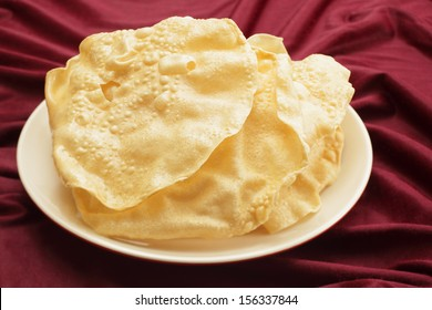 A pile of poppadoms on a plate resting on a red cloth.