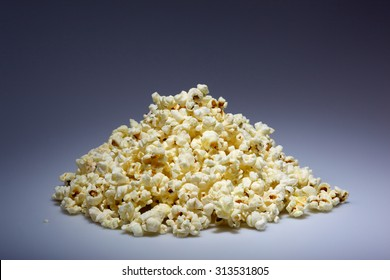 A pile of popped popcorn on a dark blue background