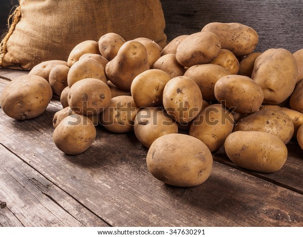 Pile of potatoes lying on wooden boards with a potato bag in the background