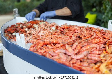 A pile of prawns, shrimp and other shellfish inside of a small boat. On the background there is a couple hands refilling this huge plate.