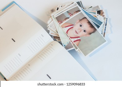 Pile of printed photographs in disorder on a white background near a photoalbum. Picture of the baby on the top.