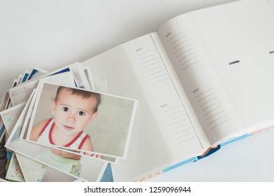Pile of printed photographs in disorder and a photoalbum on a white background. Picture of the baby on the top.