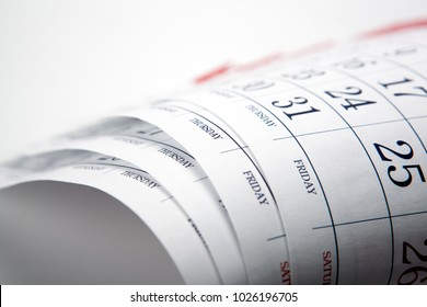 pile of printed wall calendar sheets closeup