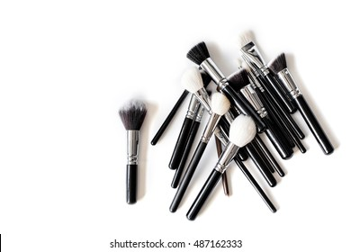 Pile of professional make up brushes of different sizes and shapes isolated on white top view.