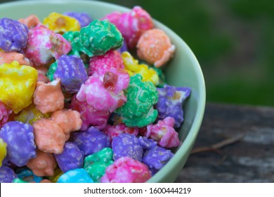 a pile of rainbow colored popcorn in a blue bowl