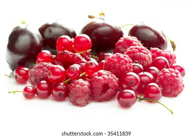 Pile of raspberries, currants and cherries isolated over white background macro shot