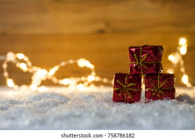 pile of red christmas presents lying in the snow with wooden background and lights
