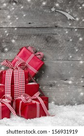 Pile of red Christmas presents, with snow on grey wooden background
