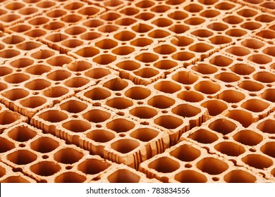 Pile of red hollow bricks with large holes forming a repetition geometric pattern similar to honeycomb background. Photo perspective from above.