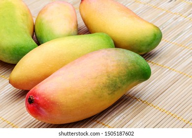 A pile of ripe ivory mangoes on a bamboo mat