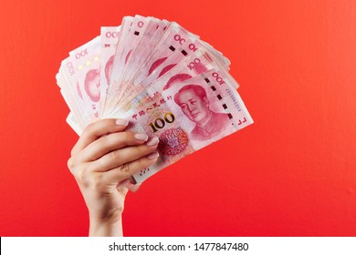 A pile of RMB banknotes of Chinese yuan money in a female hand on a red background