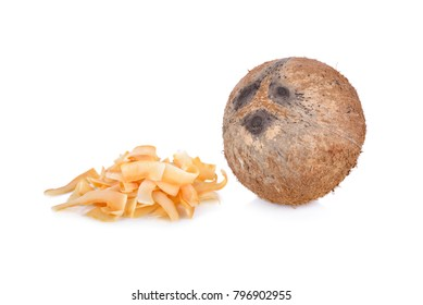 pile of roasted coconut chips and whole coconut on white background