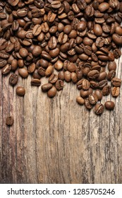 Pile of roasted coffee beans on old wooden background. Top view point.
