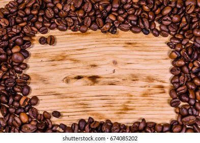 Pile of the roasted coffee beans on rustic wooden table. Top view
