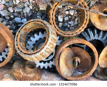 Pile of roller bearings and gear wheels on ground rustying away.