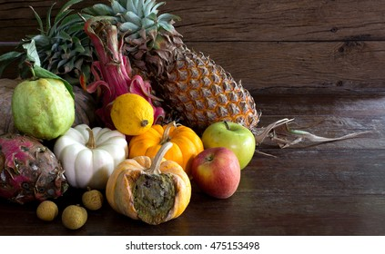 Pile rot and withered of fruits in dim light on old wooden plate / Still life style and visual art