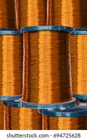 Pile of round enameled copper wire or magnet wire in spool packaging, used for transformer manufacturing
