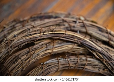 Pile of round vine wreath on distressed wooden surface background. Closeup of dry grapevine twigs texture in semicircular shape. Backdrop in shades of brown. Tangled vine texture on grunge board.