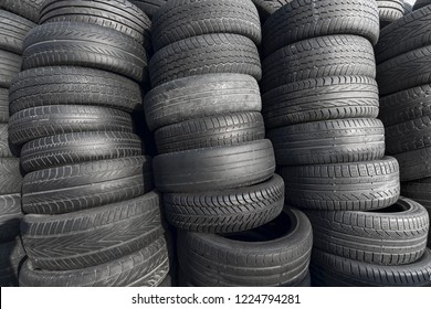 Pile of rubber automotive tyres, car tyres recycling background