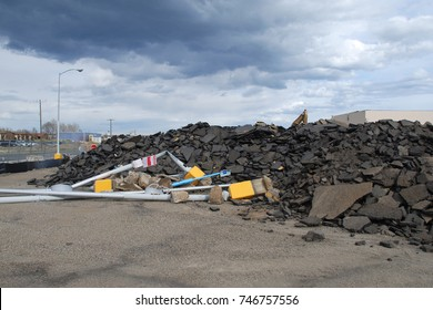 Pile of rubble (asphalt and twisted metal lamp posts) sit next to a big box store that is being demolished