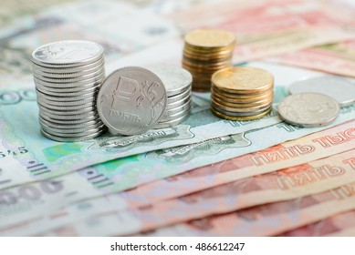 pile of Russian coins are in denominations of one and five thousand rubles in front of them a coin with the symbol of the ruble â?½