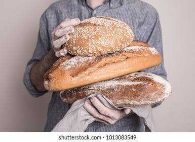 Pile of rustic crusty loaves of bread in a strong baker man's hands - closeup. Natural light, rural or country mood.