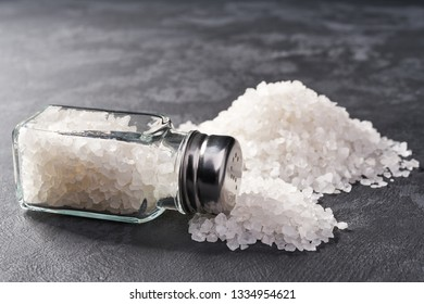 Pile of salt and salt shaker on black table,  with copy space.Sea salt.