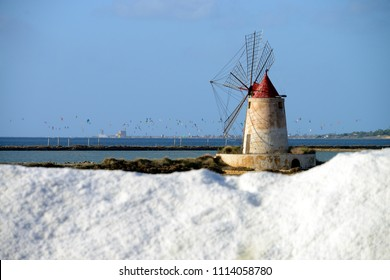 Pile of salt with traditional salt manufacturing windmill in the background, Saline di Trapani, Sicily, Italy