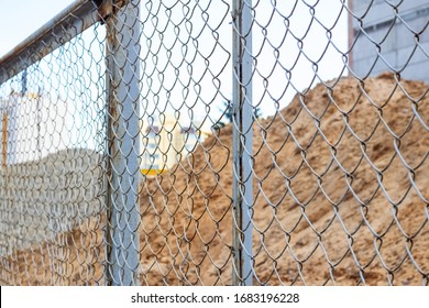 Pile of sand at construction site behind metal fense
