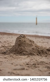 a pile of sand that used to be a sandcastle on a sandy beach