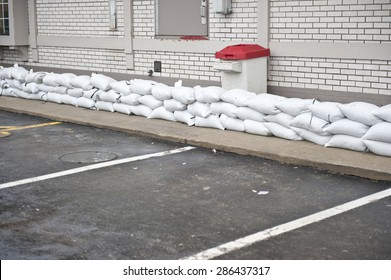 A pile of sandbags stacked to protect a restaurant on a cloudy day.