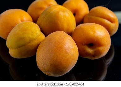 A pile of scattered apricots lie with reflection on a black glass