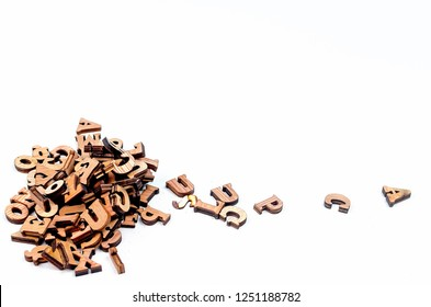 pile scattered mixed brown wooden letters of the English alphabet on white background, copy space