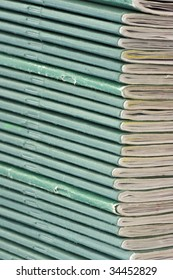 A pile of school exercise books with green covers