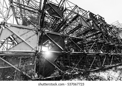 A pile of scrap metal in the snow. Several old building cranes. Heavy industry. Black and white.