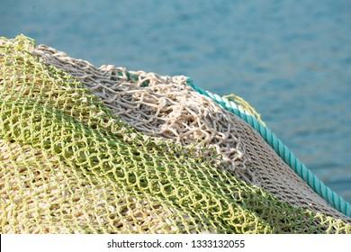 Pile of sea fishing nets with a sea background.