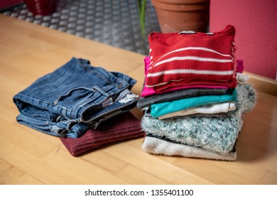 pile of second hand clothing on floor in living room