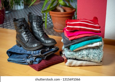 pile of second hand clothing and  shoes on floor in living room
