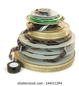 Pile of several types of movie film reels (35mm, 16mm, 8mm) and two cans, isolated over white, with clipping paths