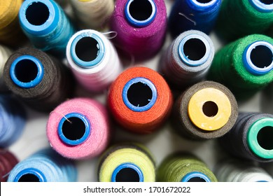 A pile of sewing reels with threads of different colors. Closeup. Top view. Background