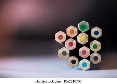 Pile of sharp coloured drawing pencils on table. Rainbow colors - red, yellow, blue, green, purple. Concept of art, crafts and kids having fun.