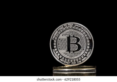 Pile of shining metal BTC bitcoin coins on black background.