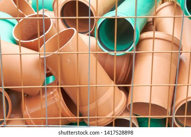 A pile of short plastic pipes lies in a grid box.
