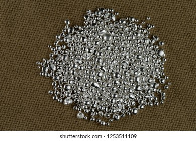 A pile of silver grains on the background to the coarse texture of the textile.