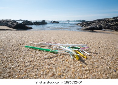 Pile of single use plastic drinking straws lying on beach. Close up. Shallow depth of field.