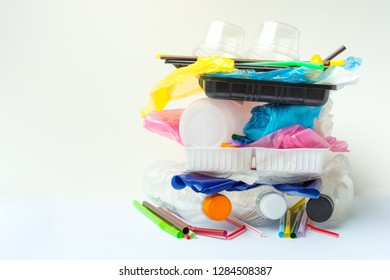 A pile of single use plastic garbage including  water bottles, drinking straws, food packages and carrier bags on white background with copy space. Pollution concept.