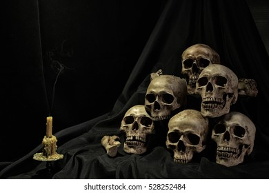 Pile of Skull and candle on black blinds in dark night / Still life image